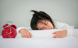 Asian women sleep on the bed with alarm clock in the morning on Stock Photos