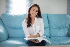 Asian women  smiling and reading a book for relaxation. Asian woman smiling and reading a book for relaxation Royalty Free Stock Images