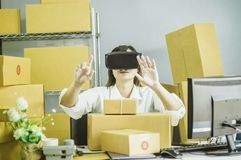 Asian women start up small business owner, are using vr to communicate , with cardboard box for packing products, in at home royalty free stock image