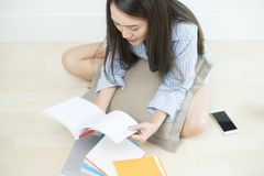 Asian women student reading books and sitting on floor of the living room at home. Royalty Free Stock Images