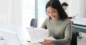 Asian women Students Smile and reading book and using notebook for helps to share ideas in the work and project. And also review royalty free stock photo