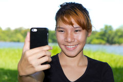 Asian women taking pictures of themselves with a cellphone Stock Images