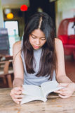 Asian women Thai teen serious focus to read pocket book in coffee shop. Stock Photography