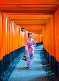 Asian women in traditional japanese kimonos at Fushimi Inari Shrine in Kyoto, Japan. Asian woman in traditional japanese kimonos at Fushimi Inari Shrine in Kyoto Stock Photos