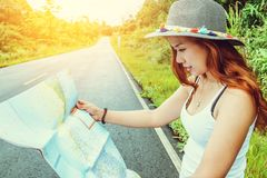 Asian women travel relax in the holiday. Take a look at the map on a rural road in the middle of nature. Thailand. Asian woman travel relax in the holiday. Take stock photo