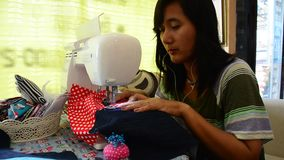 Asian women use machine sewing clothes stock footage