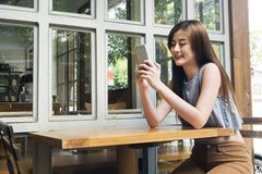 Asian women use smartphone in cafe shop. Stock Photos