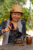 Asian women using old coffee maker. Asian woman using old style coffee grounding royalty free stock photography