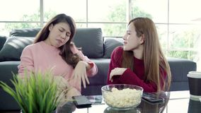 Asian women using smartphone and eating popcorn in living room at home, group of roommate friend enjoy funny moment. stock video footage