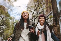 Asian women walking on street holding coffee. Smiling women in winter wear walking on street drinking coffee. Asian tourist women walking around the city on a stock photos