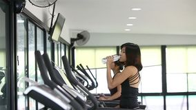 Asian women walking on treadmill gym workout. Clip of Asian women walking on treadmill gym workout stock video footage