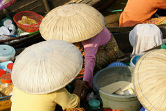 Asian women wearing big round beige colored hats sitting in and selling from their small wooden boats on a floating market. Stock Photo