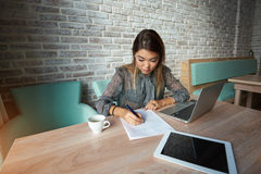 Asian  women writing pen in the contract. Beautiful young female student fills out the test while having lunch in the cafe.charming  Asian  woman writing pen in Royalty Free Stock Image