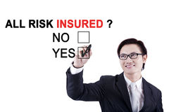 Asian worker approving all risk insured. Asian male worker using a marker while approving about a question of all risk insured on the whiteboard Royalty Free Stock Photography