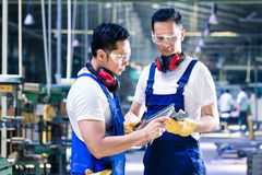 Asian worker checking work piece in production plant Stock Image