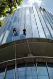 Asian worker climb on building, dangerous job Royalty Free Stock Image