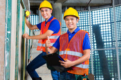 Asian worker controlling building on construction site. Asian Indonesian builder or craftsman and supervisor with hardhats, checklist and measure tape Stock Photos