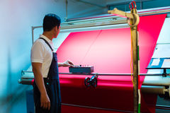 Asian worker controls fabrics in textile plant Royalty Free Stock Photo