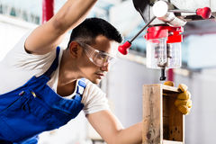 Asian worker on drill in production factory. Asian worker on drilling machine in production factory or manufacturing plant Stock Image