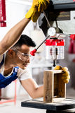 Asian worker on drill in production factory royalty free stock images