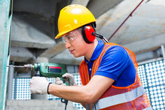 Asian worker drilling in construction site wall. Asian Indonesian builder or worker drilling with a machine or drill, ear protection and hardhat or helmet  in a Stock Image