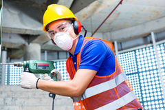 Asian worker drilling in construction site wall Royalty Free Stock Photography