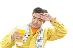 Asian worker drinking beer Stock Photo