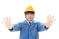 Asian worker making stop sign. Dissatisfied Asian worker isolated on white background Stock Photo