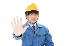 Asian worker making stop sign. Dissatisfied Asian worker isolated on white background Royalty Free Stock Image