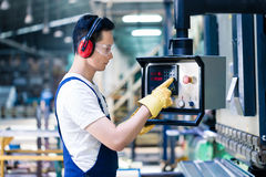 Asian worker operating CNC metal skip in factory. On the machine floor Royalty Free Stock Photos