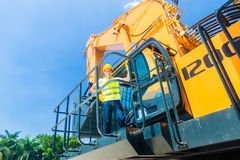 Asian worker on shovel excavator construction site Royalty Free Stock Photo