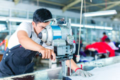 Asian worker using a machine in a factory. Indonesian worker using a cutter - a large machine for cutting fabrics - in a asian textile factory, he wears a chain