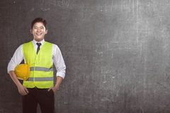 Asian worker wearing safety vest and yellow helmet Royalty Free Stock Photo