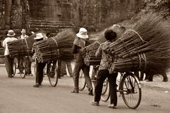 Asian workers transporting brooms