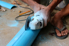 Asian workers use circular saw cutting the PVC pipe. Asian workers use electric circular saw cutting the PVC pipe Royalty Free Stock Photo