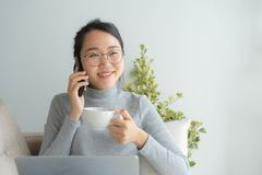 Asian working woman on her face wear glasses , smile , talk on telephone .Young business woman is drinking coffee and looking. Outside the window in the morning stock photos