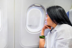 Asian wowan rest hand on chin in airplane cabin near window seat Royalty Free Stock Image