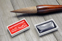 Asian writing brush and ink for calligraphy. On wooden background Stock Image