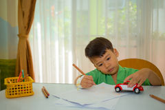Asian 3 years kid drawing and play toy carl to relax Royalty Free Stock Images