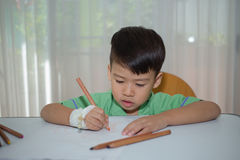 Asian 3 years kid drawing on white paoer with color pencil to re Royalty Free Stock Images
