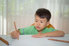 Asian 3 years kid drawing on white paper with color pencil Royalty Free Stock Photography
