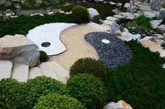 Asian Yin and Yang symbol of contrary and complementary forces made as stone decoration with pathway in Mu-Shin garden. Afternoon sunshine during summer season stock photo