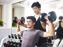 Asian young adult working out in gym Royalty Free Stock Images
