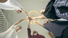 Asian young adult men putting hands together to show determination and unity