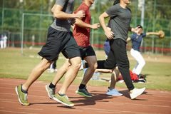Asian young adults running on track. Four asian young adults training running on track Stock Images