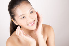 Asian young beautiful woman with flawless complexion smiling and touching face Stock Images