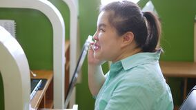 Asian young blind person woman smiling using smart phone with voice assistive technology for disabilities persons in workplace