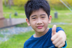 Asian young boy. A cute Asian Thai young boy with thumb-up Royalty Free Stock Images
