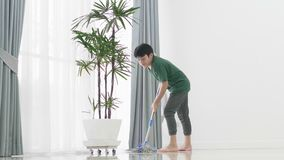Asian young boy help family cleaning the house using a mop. Asian young boy help family is cleaning the house using a mop stock video footage