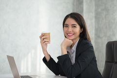 Asian young business girl  holding a coffee cup in hand, sitting. In the office while smiling at you Stock Photography